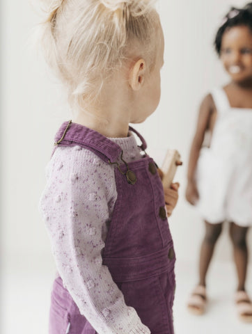 Toddlers wearing Jamie Kay Flourish collection outfits - Cord Overall Dress in Lavender and Lilac Fleck Dotty Knit sweater and Sweet Pea Floral Ava Dress