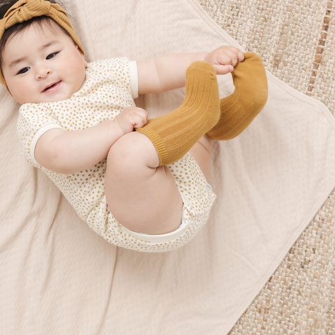 Baby in Quincy Mae Retro Romper Ocre Headband and Ocre Socks
