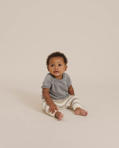 Quincy Mae Spring Summer 21 Drop 2 - older baby sitting up in a studio shoot wearing the terry cloth tee in ocean with the retro stripe terry sweatpants