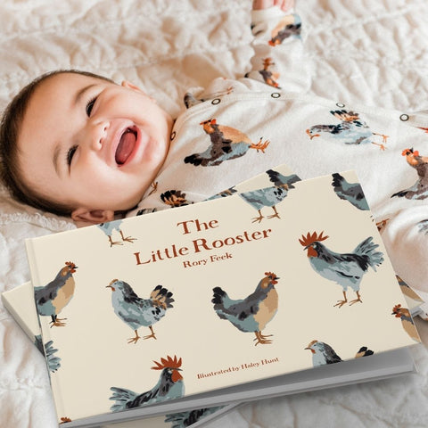 MilkBarn Kids Chicken print footed romper on a little baby laying on the new chicken print organic cotton crib sheet with the new The Little Rooster Book, arriving early spring 2021.