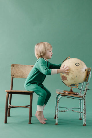 Fin & Vince Chapter 3 Solid Essentials collection - toddler wearing forest waffle longjohns while sitting on vintage wooden chair looking at globe