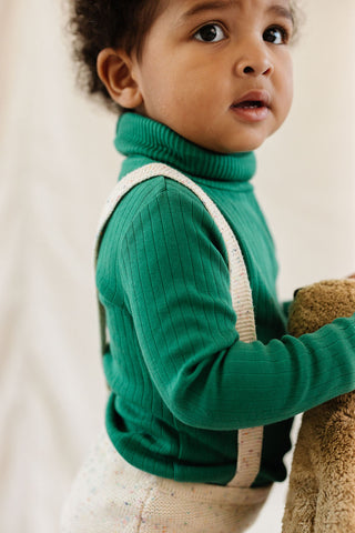 Fin & Vince Chapter 3 Solid Essentials collection - toddler wearing emerald ribbed turtleneck with confetti suspender pants