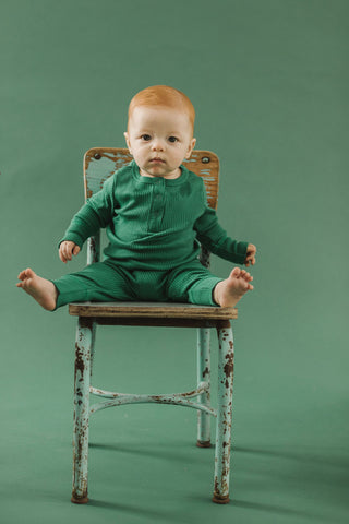 Fin & Vince Chapter 3 Solid Essentials collection - toddler wearing emerald ribbed henley with drop needle pants sitting on vintage chair