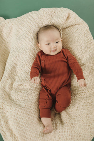 Fin & Vince Chapter 3 Solid Essentials collection - baby on milk blanket wearing gingerbread wrap one piece coverall