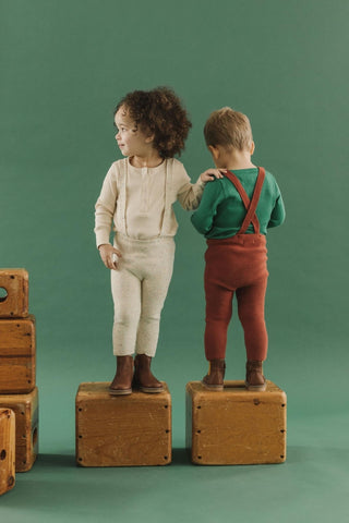 Fin & Vince Chapter 2 - toddlers wearing knit suspender pants and wrap cardigans in confetti and gingerbread standing on suitcases.