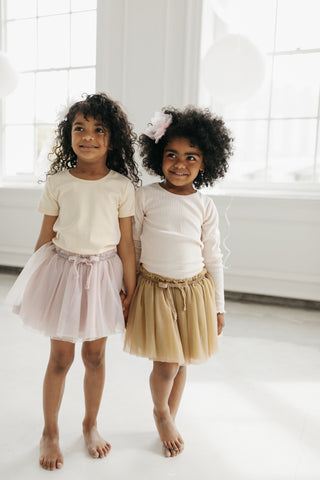 Two girls holding hands wearing Jamie Kay Carousel collection pieces, including the tutu in champagne with the long sleeve Charlie top in  honey peach stripe and the blush tutu with a short sleeve stripe tee.