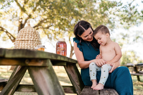 Milkbarn Kids lifestyle photo of little toddler boy wearing new Spring 2021 bumblebee print bamboo leggings while sitting at picnic table on mom's lap with jar of honey