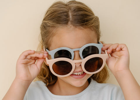 Grech & Co New 2021 Summer sunglasses lifestyle shot - little girl wearing the blue and pink matte round sunnies made of recycled plastic
