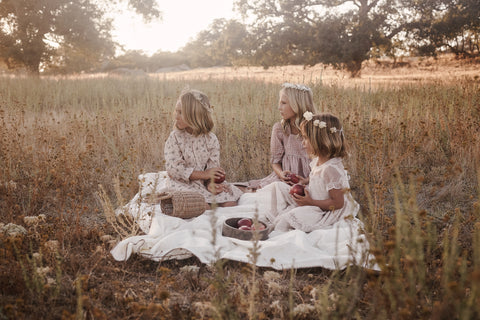 Noralee lifestyle photo - three girls in a field at sunset wearing debut collection dresses from the Noralee Winter 2020 collection