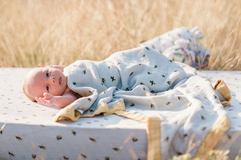 Lifestyle photo of infant baby on new Milkbarn Kids bamboo crib sheet in bumblebee, covered in the Big Lovey in Bumblebee in a wheat field