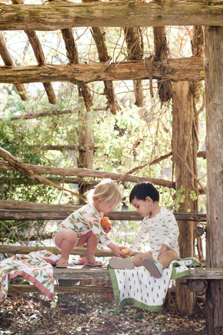 Milkbarn Kids Lifestyle Photo of two toddlers wearing new organic cotton prints, Grasshopper and Peaches, while sharing a peach on the Grasshopper Big Lovey Blanket in the romper and long sleeve one piece bodysuit.