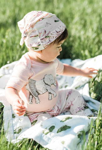 MilkBarn Kids outfit - baby on grass and Leap Frog print Big Lovey blanket wearing tutu elephant applique one piece and water lily print hat and bamboo leggings