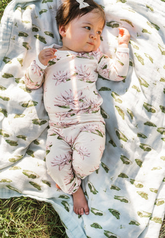 MilkBarn Baby in Water Lily bamboo long sleeve onesie one piece and bamboo leggings on leap frog swaddle blanket