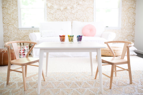 Milton & Goose crescent chair pair in natural and children's play table in white in a beautiful living room topped with containers of neatly arranged crayons. Non-toxic, solid wood, and made in the USA play furniture for children.