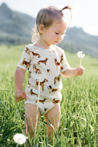 Baby in MilkBarn Kids one piece in natural dog print while holding a dandelion