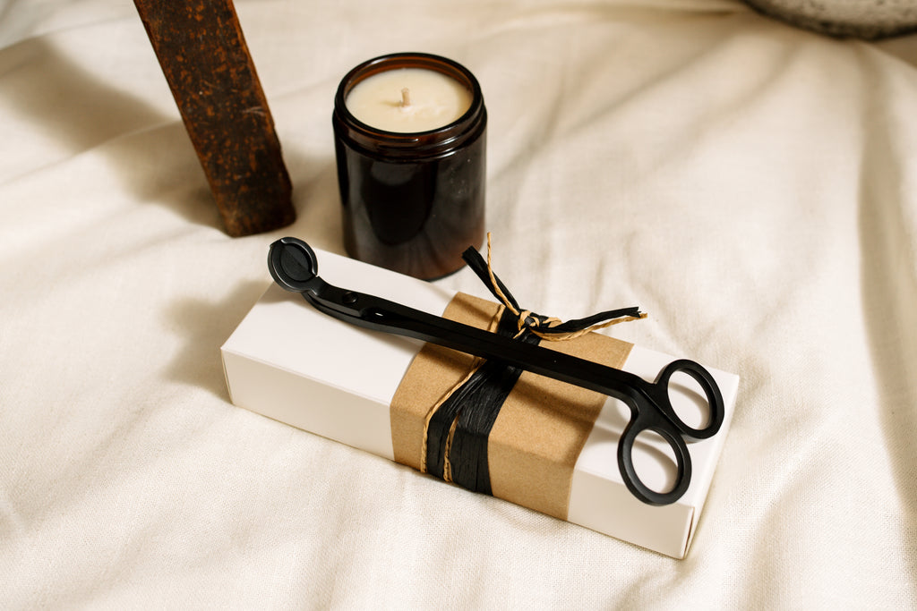 Black metal candle wick trimmers, sitting on a gift box and next to a small natural soy wax candle