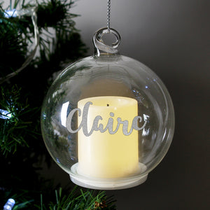 Personalised clear glass round Christmas bauble which has a battery operated cream yellow LED candle inside.  The bauble can be personalsied with a name in a silver hand-written styled modern font and comes with a silver thread to hang it up.