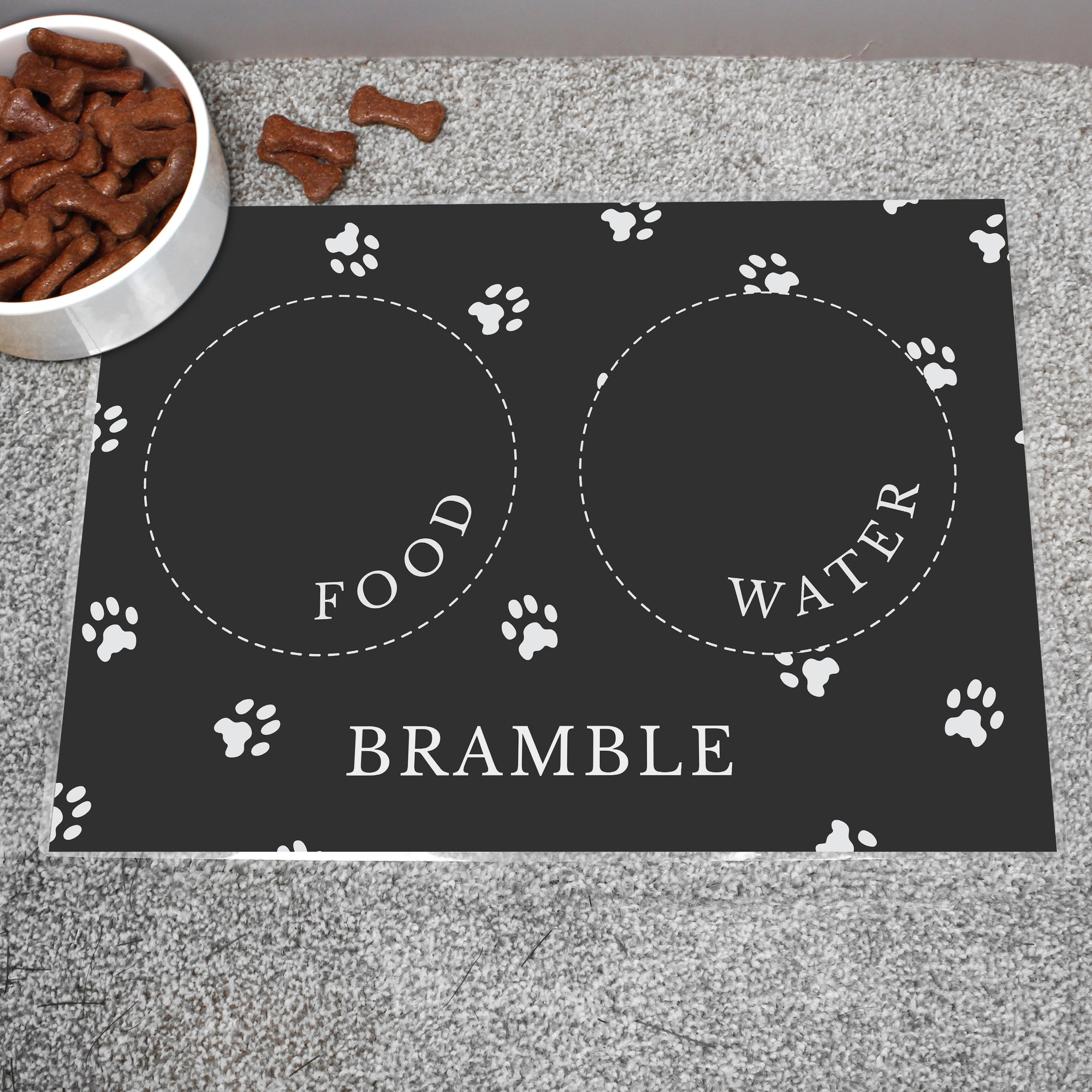 Image of a personalised black pet platemat with white paw print design to protect floors