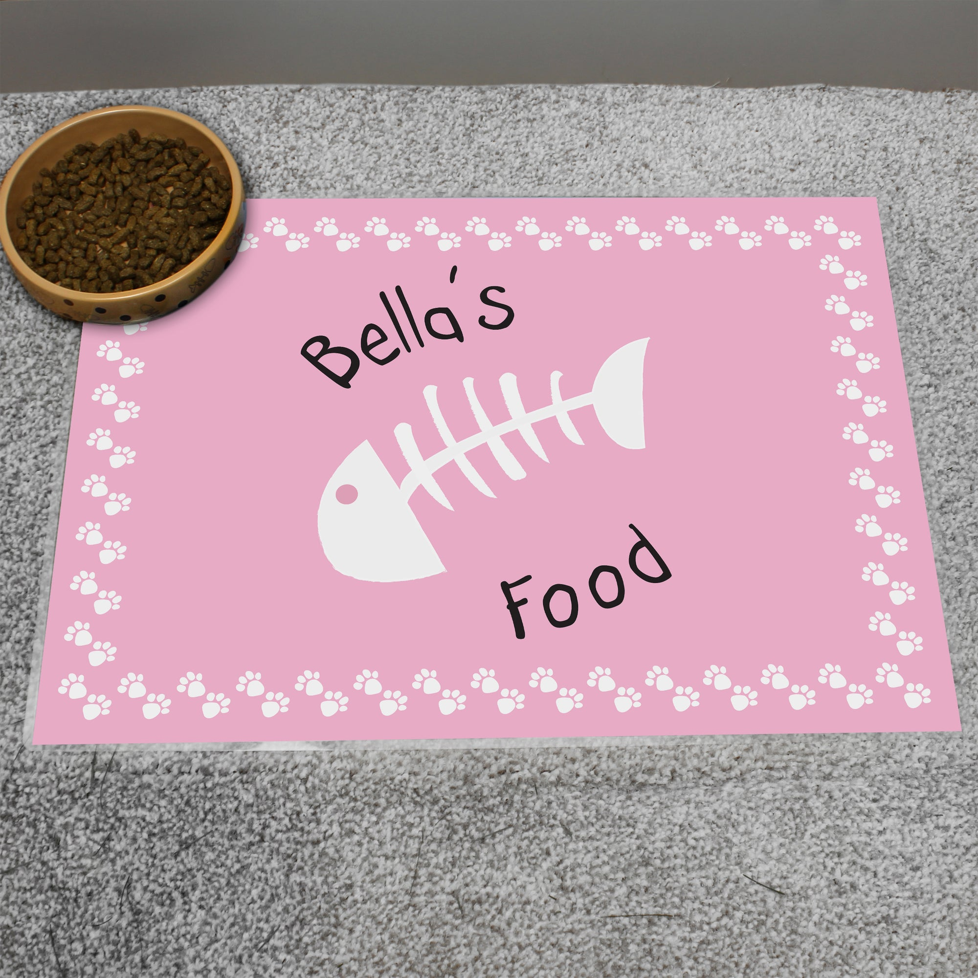 Personalised laminated pink placemat for a cat. The mat has a white illusatration in the middle of some fish bones and white paw prints around the outside, and can be personalised with your cat's name followed by the word 'food' which is a fixed part of the design.