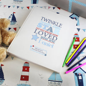 Personalised photo album with the text 'twinkle twinkle little star do you know how loved you are' printed on the front cover in various fonts and sizes in different shades of blue and red. The cover can be personalised with a name and message or celebration details of your choice. Internally the album has approximately 30 pages interleafed with tissue.