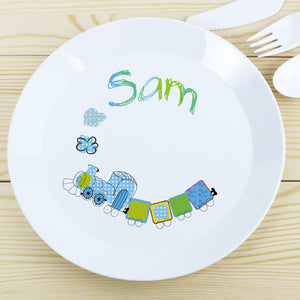 Image of a white plastic BPA free childs personalised plate. The plate is white with a rim and in the centre of the plate is a cartoon drawing of a blue and green train with smoke coming out of the train's funnel. The plate can be personalised with a name up to 12 characters which will be printed above the steam in a mixture of blue and green. The plate is part of a set and comes with a cup and cutlery set in the same theme.