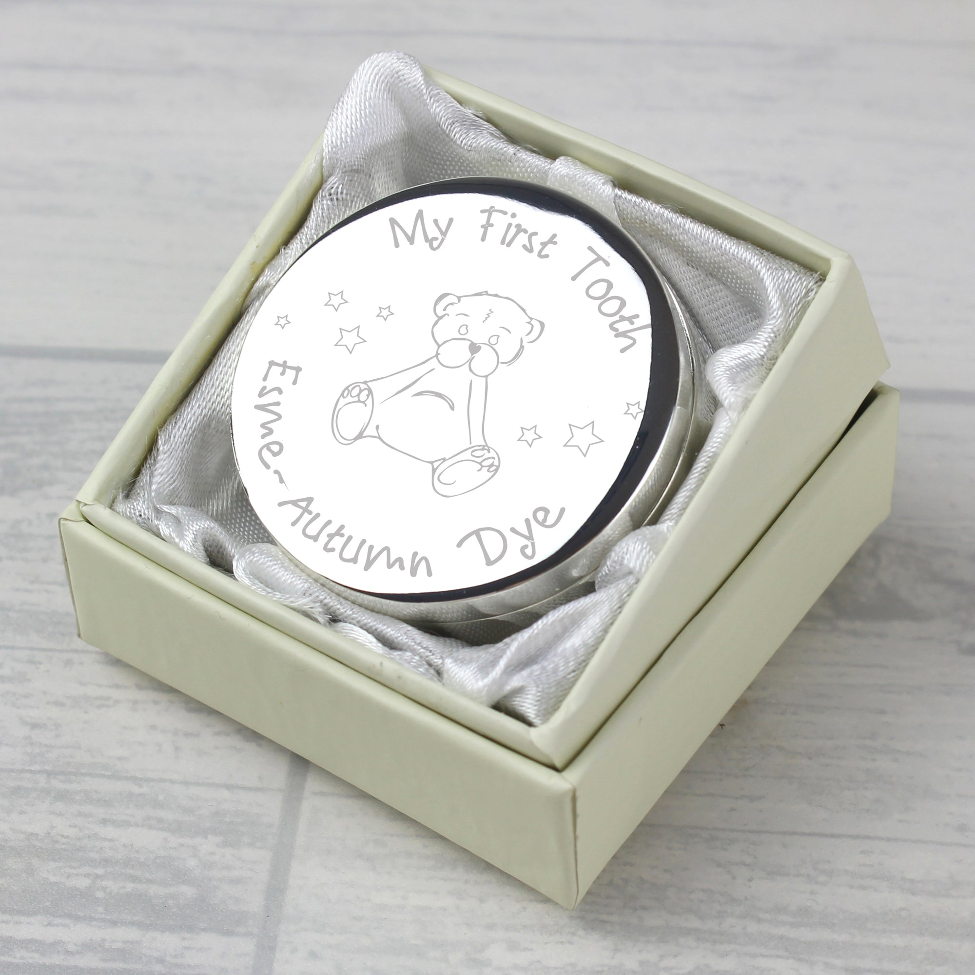 A round silver coloured metal trinket box. The lid of the box has an image of a teddy bear engraved in the centre and above it is the wording 'My First Tooth'. Your own wording of up to 20 characters can be engraved below the teddy, usually a name or a name and date. The trinket box comes in a small presentation box.