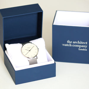 Image of a man's watch in a blue presentation box. The watch can be engraved on the back with your own handwriting. The watch is made by The Architect Watch Company London and has a large white face and a stainless steel mesh strap. The rear of the watch can be engraved with your message written in your own handwriting.