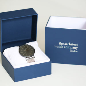Image of a man's watch in a blue presentation box. The watch can be engraved on the back with your own handwriting. The watch is made by The Architect Watch Company London and has a large black face and a stainless steel mesh strap. The rear of the watch can be engraved with your message written in your own handwriting.