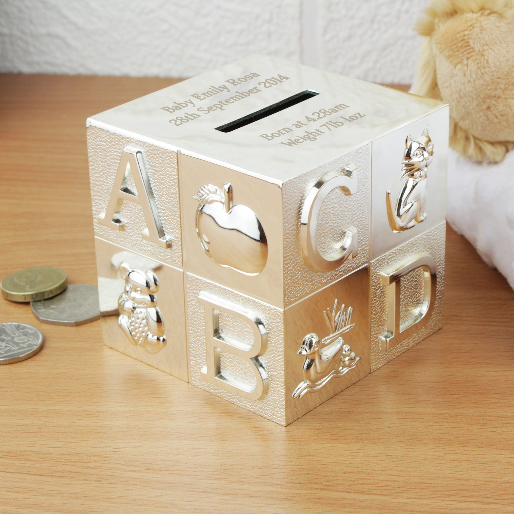 A silver-plated engraved square money box. The money box has an ABCD design on the four sides and the top of the money box has the money slot in it. The money box can be engraved with two lines of text above the money slot and two lines of text below the money slot. This moneybox measures 7.7cm by 7.7cm by 7.7cm.