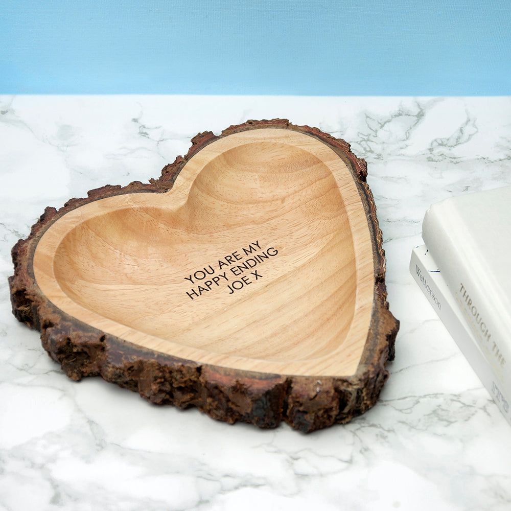 Image of a hand-carved heart-shaped wooden bowl that has a rustic natural bark edging. The bowl can be personalised with your own message which will be engraved in an upper case font.