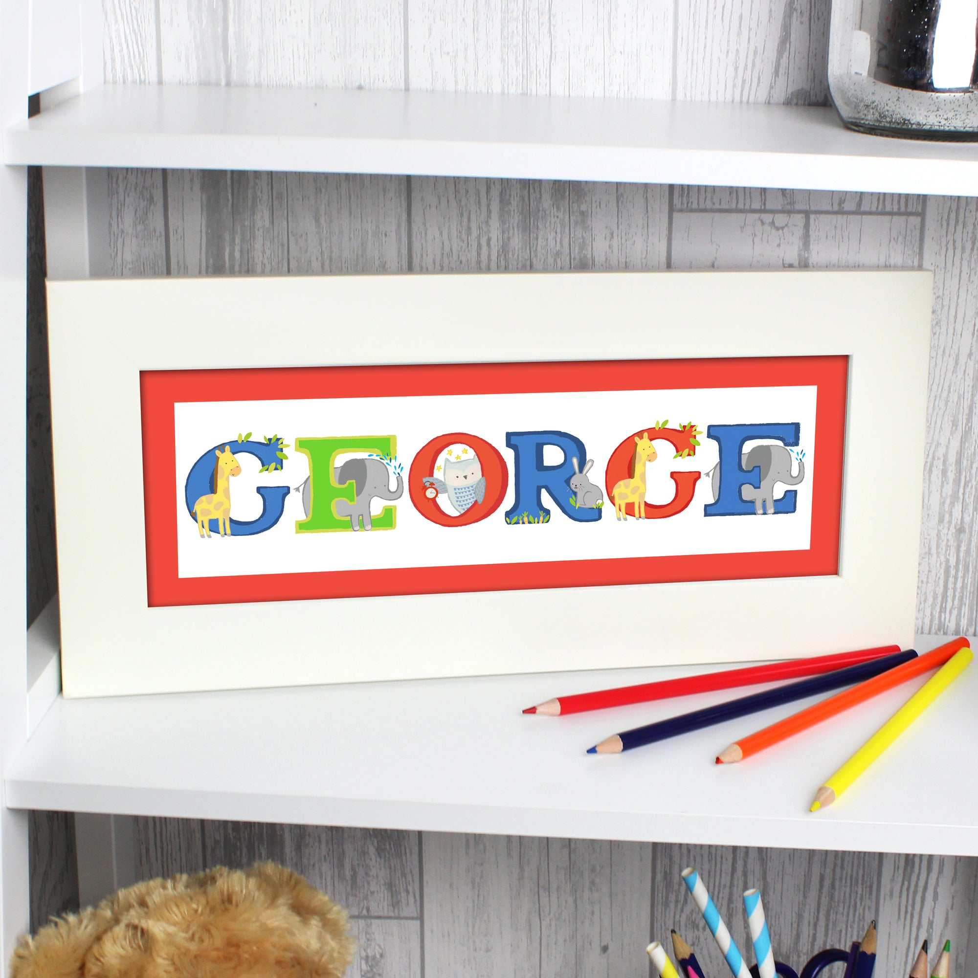 A personalised print of a name of your choice when the letters used are from our animal alphabet. Each letter is in uppercase and printed in bright colours, and intertwined with a different animal. The print comes in a wide white frame which measures approximately 16 cm high by 36 cm wide.