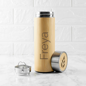 Personalised bamboo vacuum flask with a screw top lid and an optional stainless steel tea strainer insert. The flask is stainless steel double walled insulated and the outside is made from natural bamboo which can be engraved with a name of your choice.