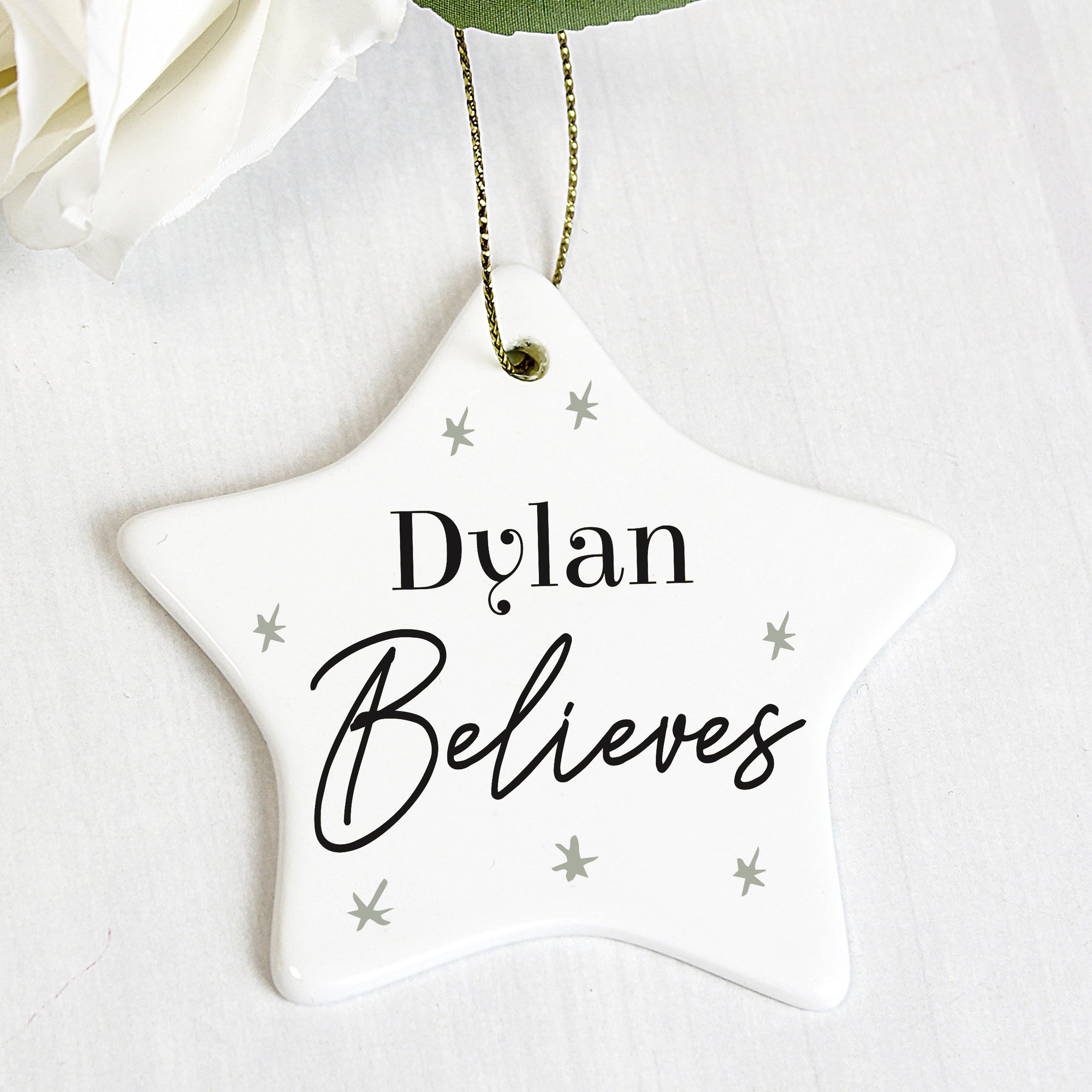 White ceramic star shaped Christmas decoration that comes with a string ready to hang. The decoration can be personalised with a name of up to 12 characters on the front followed by the word 'Believes'. The star has a small number of grey stars printed ono the front in a minimalistic hand drawn style.