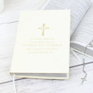 Image of a bible with white cover that can be personalised with 5 lines of your own text. A cross is printed above the text, all of which is printed in gold. The bible has a ribbon bookmark and the pages are made from 100% recycled paper.