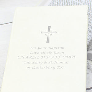 Image of a bible with white cover that can be personalised with 5 lines of your own text. A cross is printed above the text, all of which is printed in silver. The bible has a ribbon bookmark and the pages are made from 100% recycled paper.