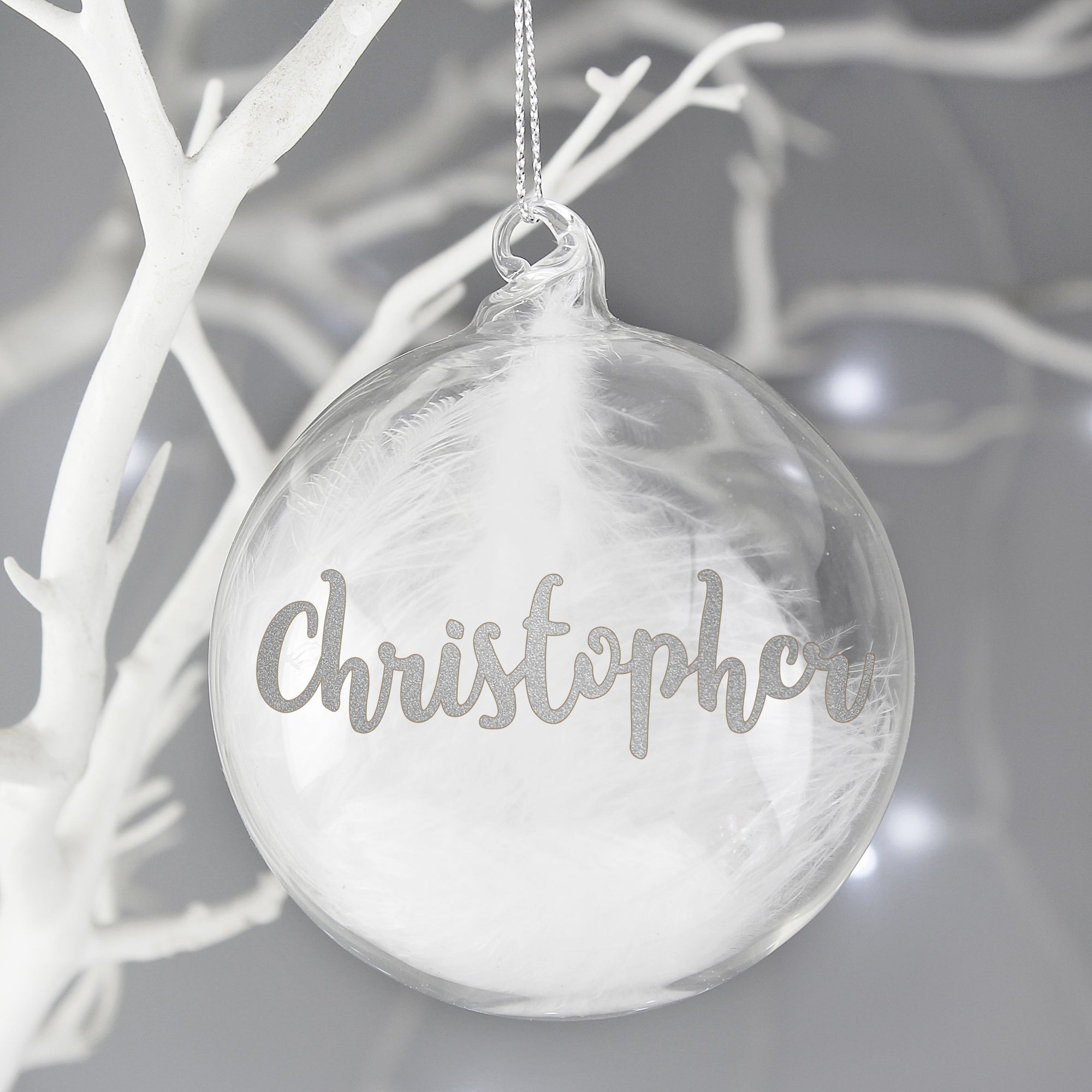 Personalised hand-made clear glass Christmas bauble that has a white feather inside it. The front of the bauble can be personalised with a name of your choice of up to 11 characters that will be printed in a silver glittery modern cursive font. The bauble comes with a string ready to hang and measures approximately 8 cm wide.