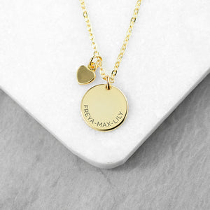Personalised gold plated necklace with a disc that can be engraved with a name or message of your choice and a small heart charm next to it. The necklace comes with a gold plated necklace.
