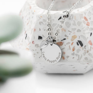 Personalised silver plated necklace with a disc that can be engraved with a name or message of your choice and a small heart charm next to it. The necklace comes with a silver plated necklace.