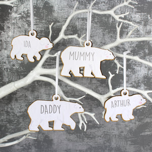 Personalised family set of four wooden polar bear decorations with two adults and two baby bears. Each bear is painted white and can be personalised with a name of up to 12 characters which will be printed on each bear in a modern grey uppercase font.