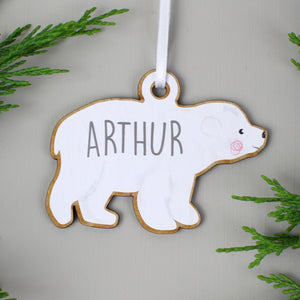 Personalised baby polar bear decoration as part of a family set of two adults and two baby bears. Each bear is painted white and can be personalised with a name of up to 12 characters which will be printed on each bear in a modern grey uppercase font.