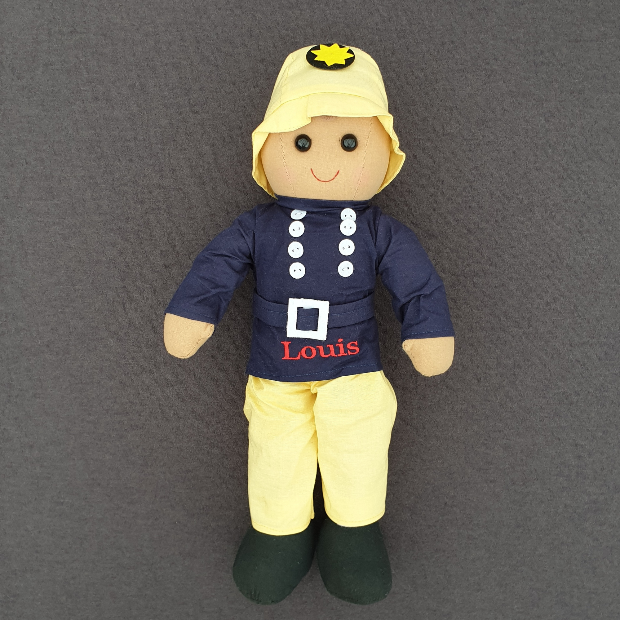 Personalised fireman ragdoll. The doll is wearing yellow trousers and a yellow hat along with a navy blue tunic with a belt and white buttons. The doll is made from cotton and measures approximately 40 cm in height.