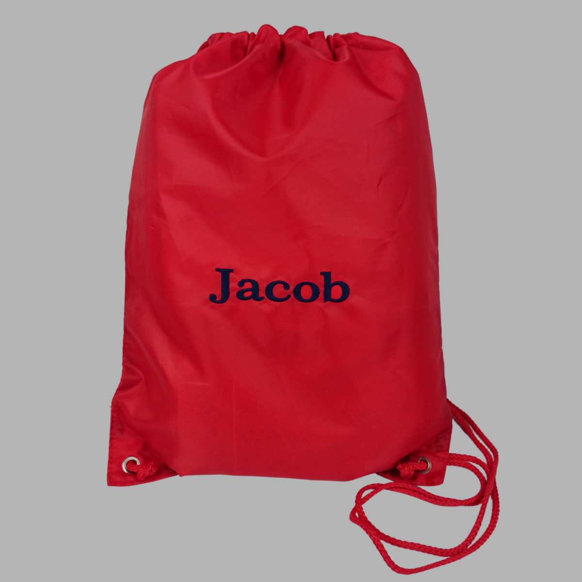 Personalised PE or swimming bag shown in red with a name embroidered in navy blue thread.