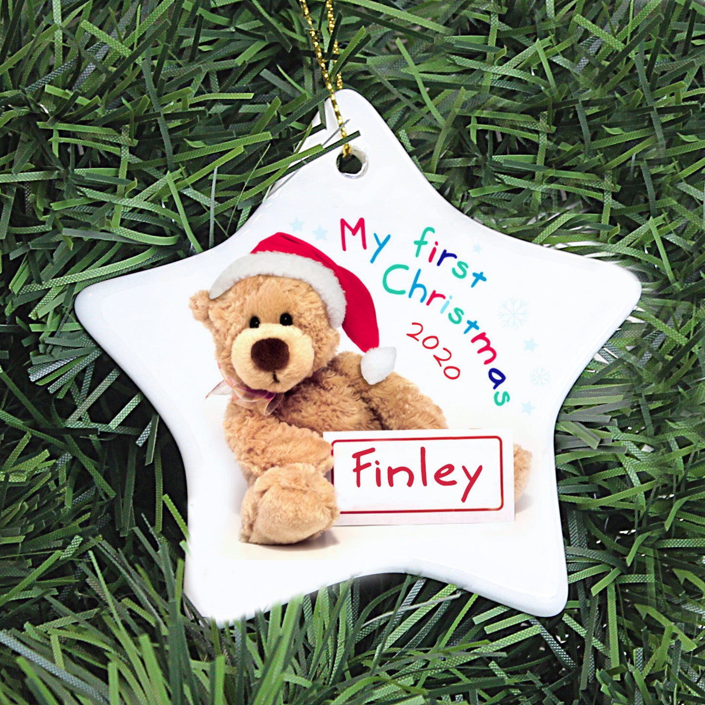 Personalised white ceramic star shaped Christmas decoration with an image of a teddy bear wearing a red and white santa hat and holding a sign which can be personalised with a name of your choice.  Next to the bear is the text 'My first Christmas' in bright multi coloured lettering and you can also add a year which will be printed below that in red.