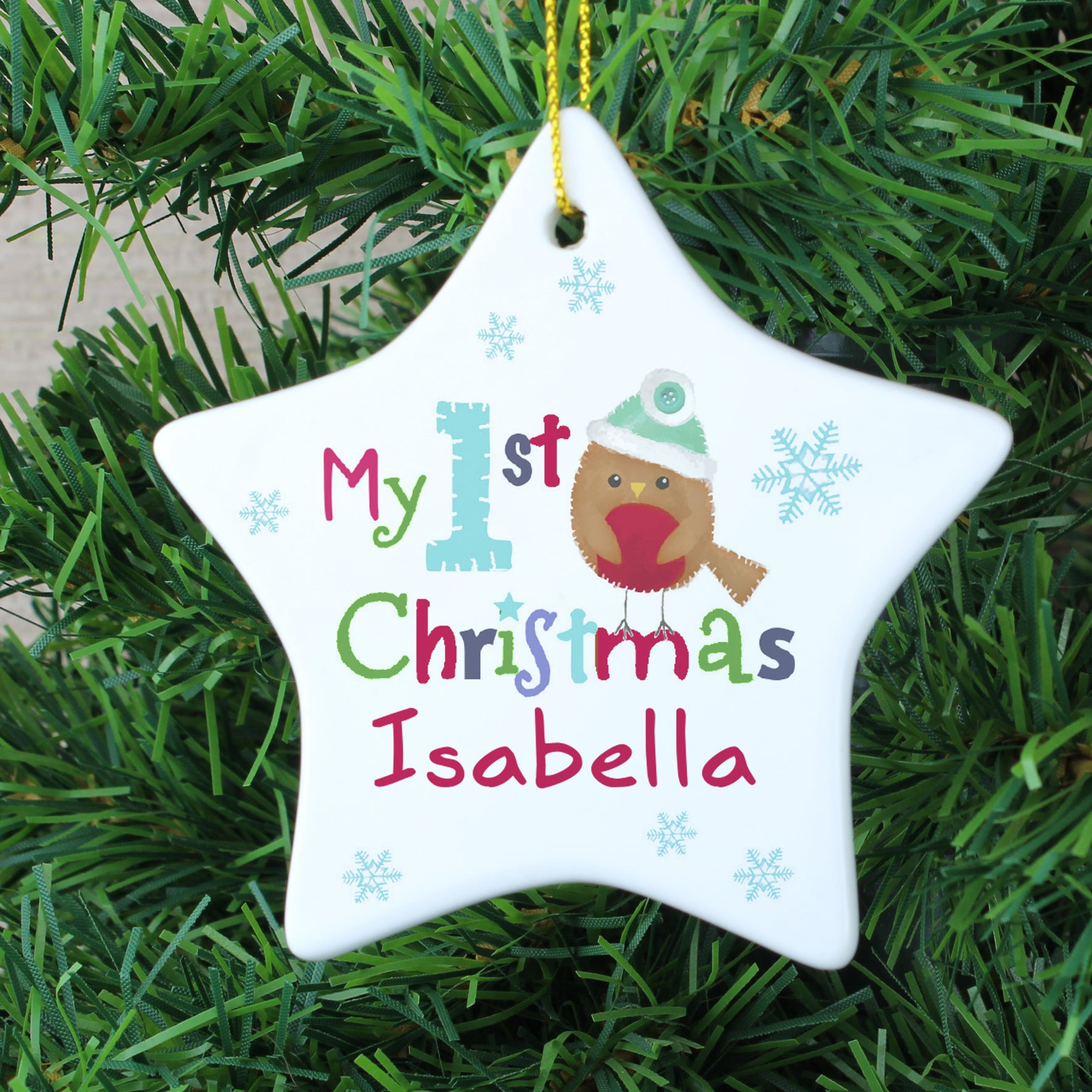 Personalised white ceramic star shaped Christmas decoration to hang on a tree featuring the words 'My 1st Christmas' on the front alongside an image of a hand-drawn robin. The front of the decoration can be personalised with a name of your choice of up to 12 characters.
