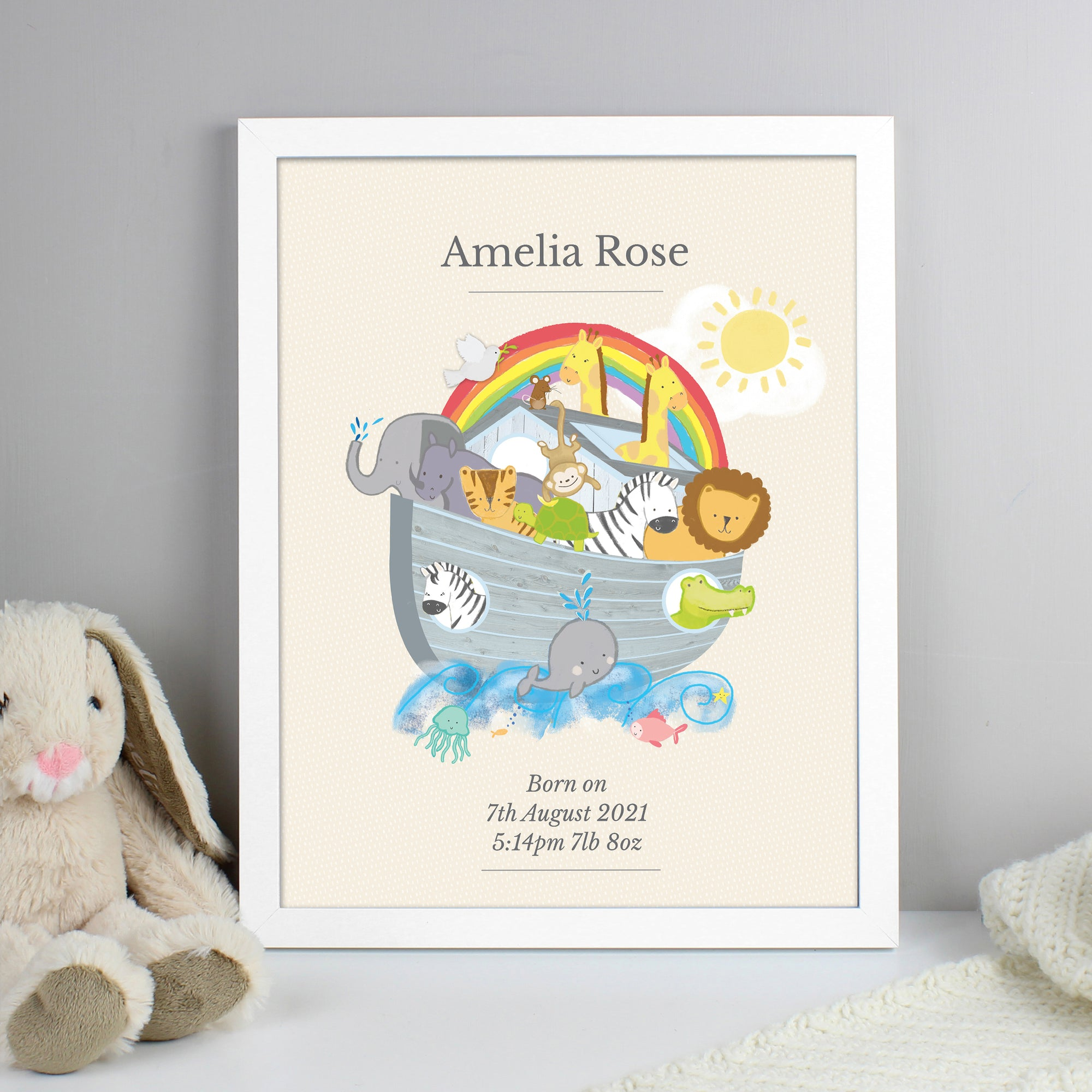 A framed print of Noah's Ark which can be personalised with a name and your own special message or birth details. The print has a cream background with a full illustration of Noah's Ark in the centre of it with animals on the deck plus swimming around the Ark.  A name can be added above the illustration of the Ark and below it you can add your own information over up to 3 lines. The print comes in a white frame and measures approximately 38 cm high and 30 cm wide.