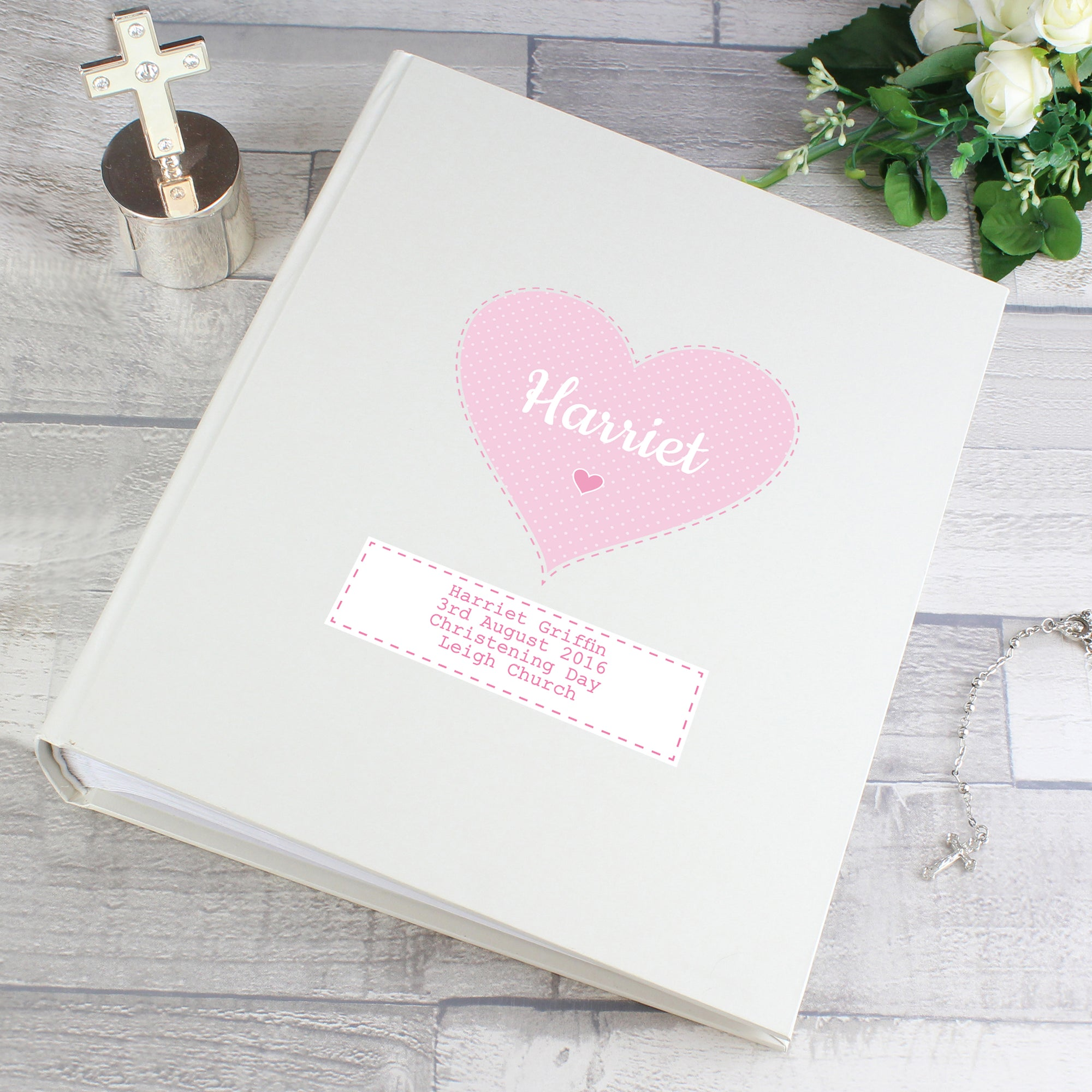 Personalised white satin sheen photo album which has a pink heart in the centre of the front cover. The cover can be personalised with a name of your choice which will be printed in a modern white font inside the pink heart. Beneath the star is a white box and you can add your own special information over up to 4 lines which will be printed in pink text.