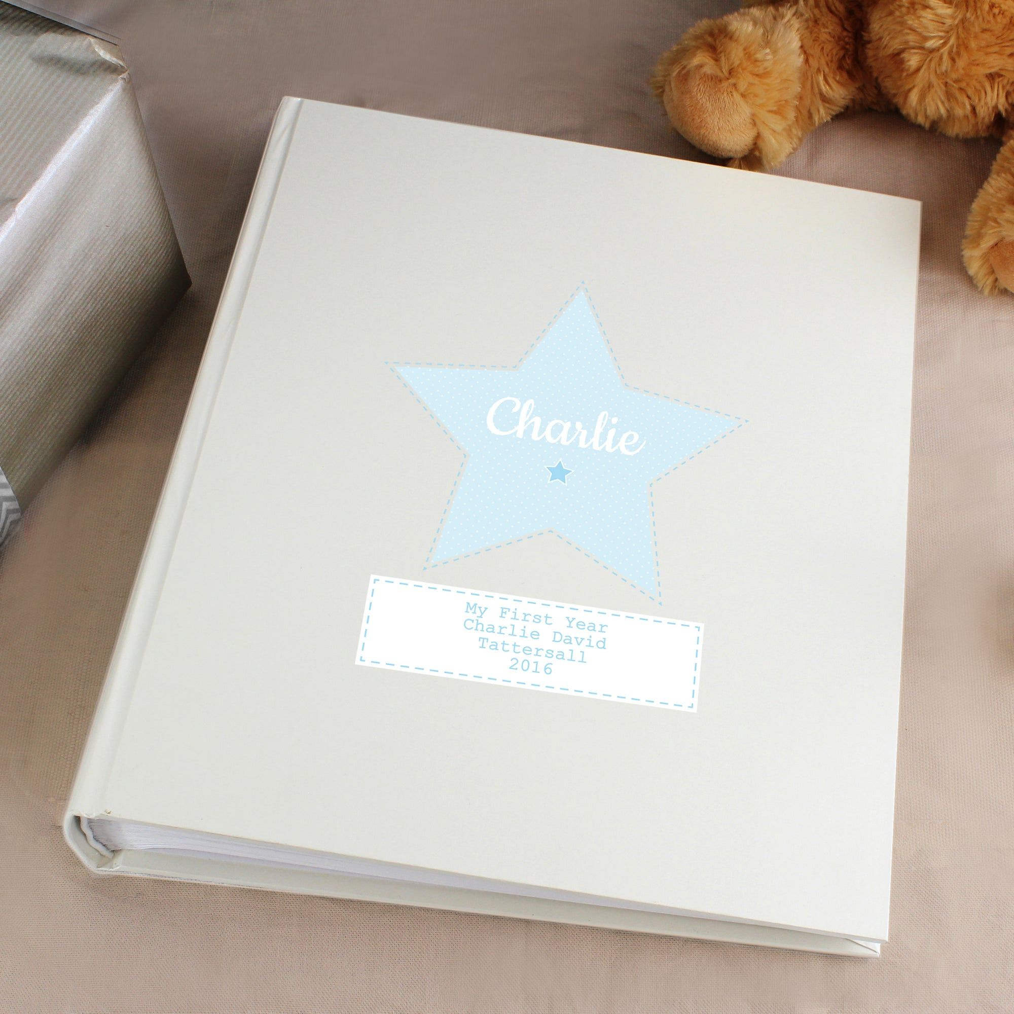 Personalised white satin sheen photo album which has a blue star in the centre of the front cover. The cover can be personalised with a name of your choice which will be printed in a modern white font inside the blue star. Beneath the star is a white box and you can add your own special information over up to 4 lines which will be printed in blue text.