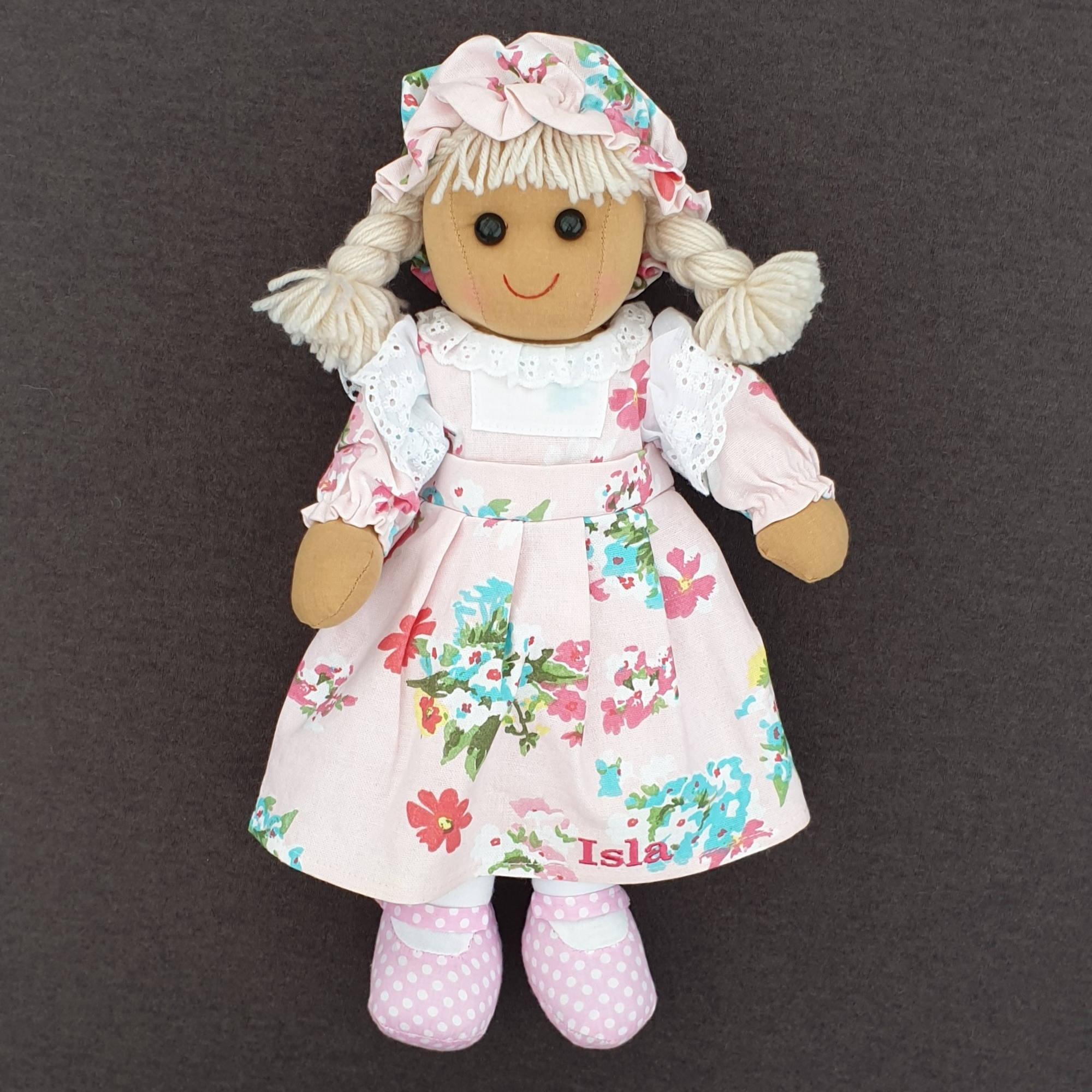 Personalised rag doll wearing a pink floral dress that can be personalised with a name of up to 10 characters plus a matching hat.  Underneath her dress she is wearing white pantaloons.