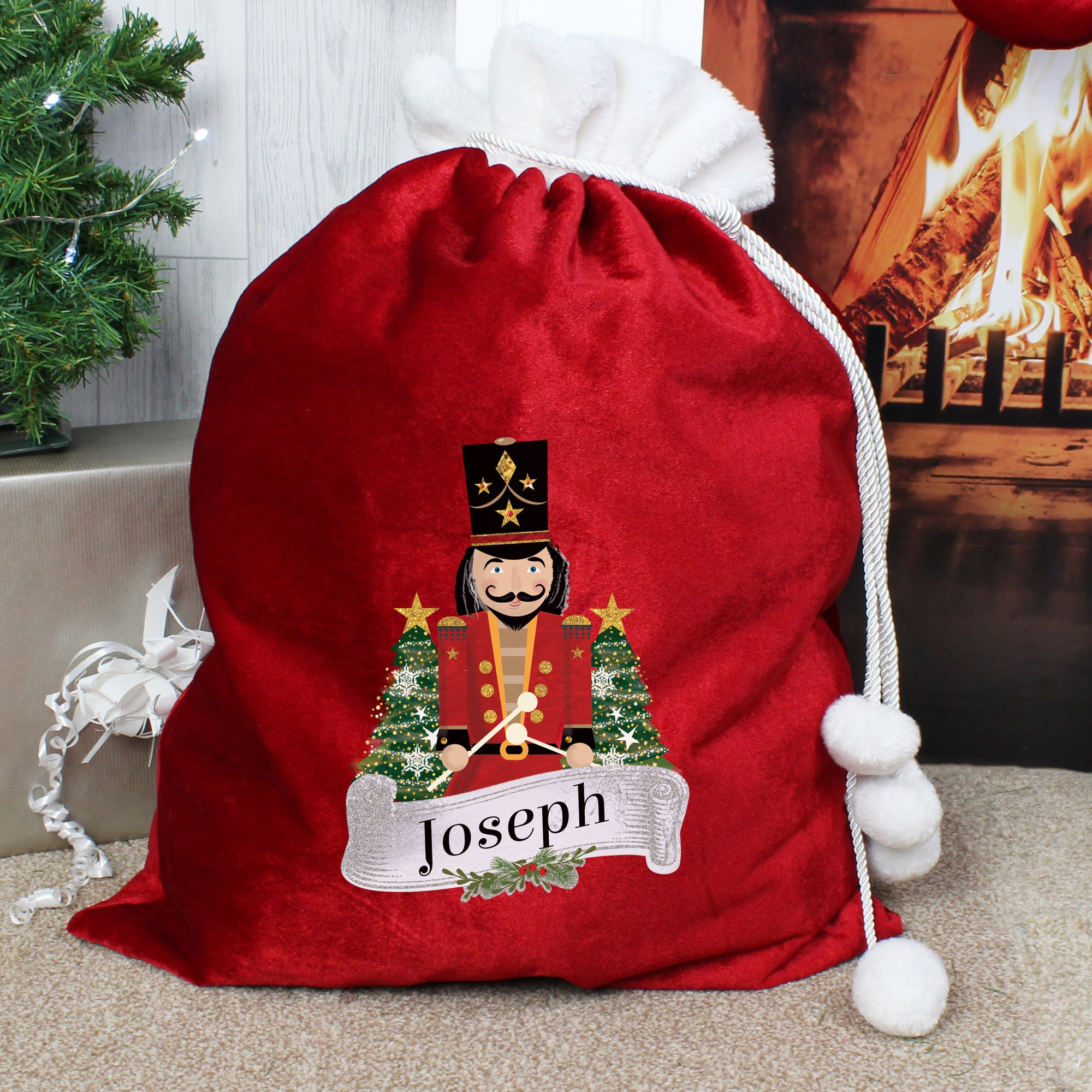Personalised Christmas present sack made from plush red fleece fabric with a white fur collar. The bag has drawstrings to close it with white pom poms on the end and the front of the sack has an image of a wooden nutcracker toy on it and it can be personalised with a name of your choice of up to 12 characters.