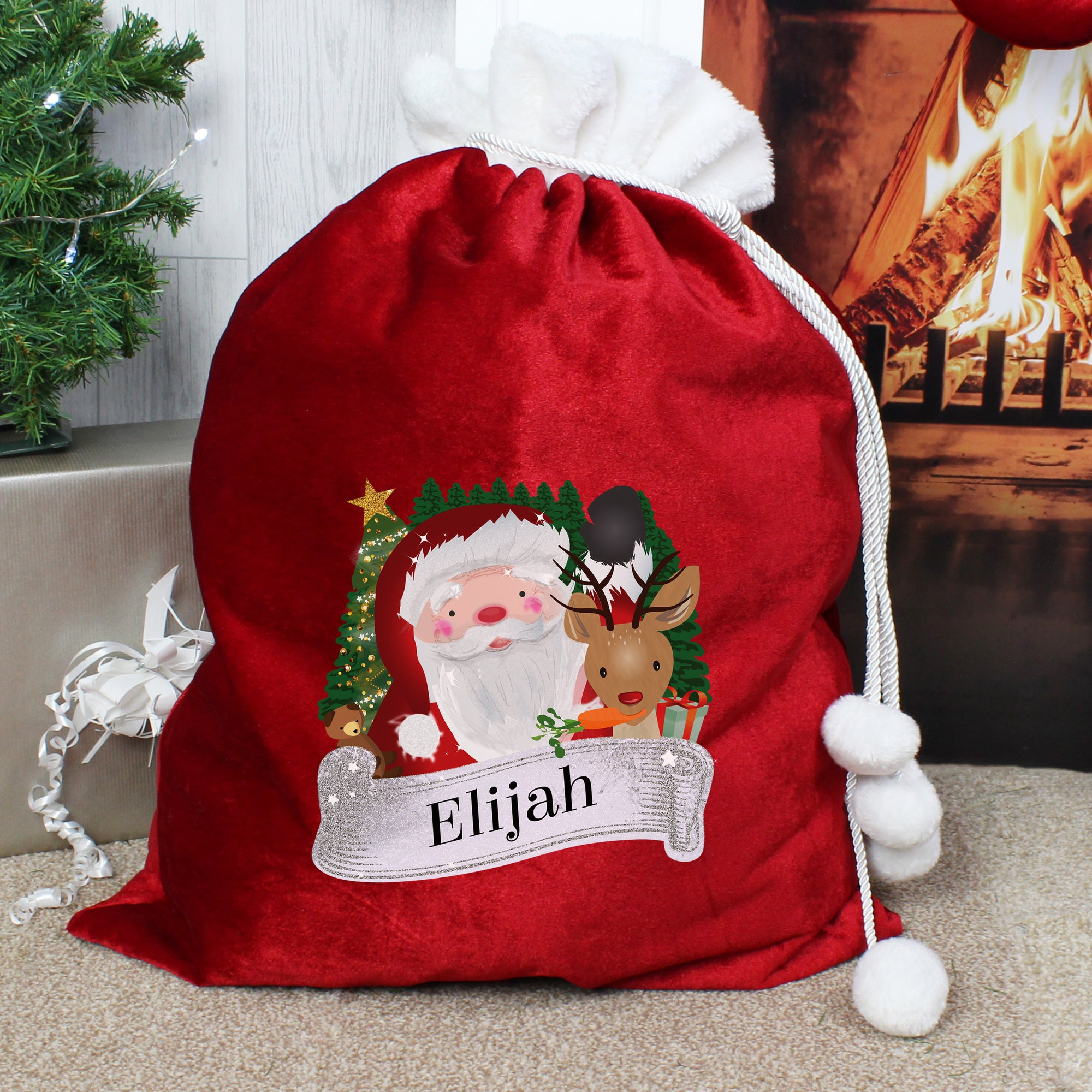 Personalised soft red velvet Christmas present sack featuring a cartoon illustration of Santa and the wording Merry Christmas. There is a white fur cuff on the top of the sack. The front of the sack can be personalised with a name of your choice of up to 12 characters which will be printed just below the illustration of Santa in a black font.